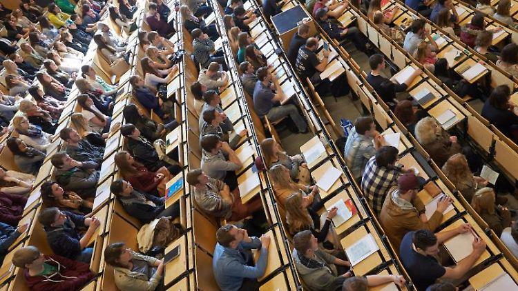 Studenten sitzen bei einer Erstsemesterbegrüßung im Hörsaal. Foto: Thomas Frey/dpa/Archiv/Symbolbild