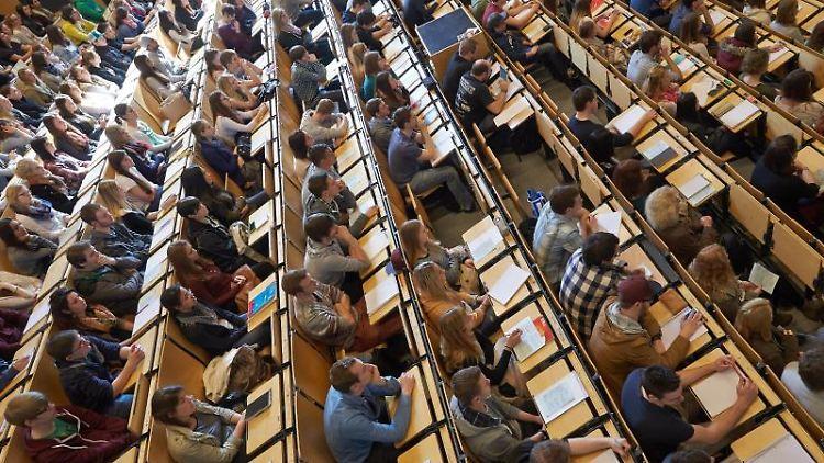Studenten sitzen bei der Erstsemesterbegrüßung. Foto: Thomas Frey/dpa