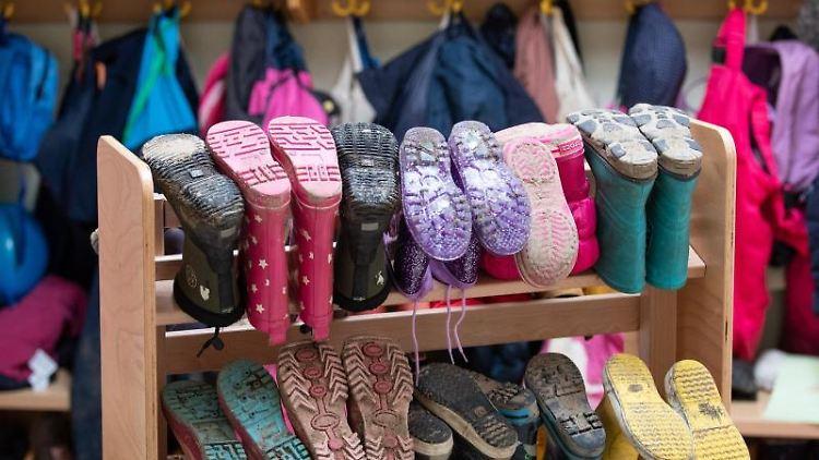 Kinderbekleidung und Stiefel sind in einer Kindertagesstätte zu sehen. Foto: Friso Gentsch/dpa/Archiv
