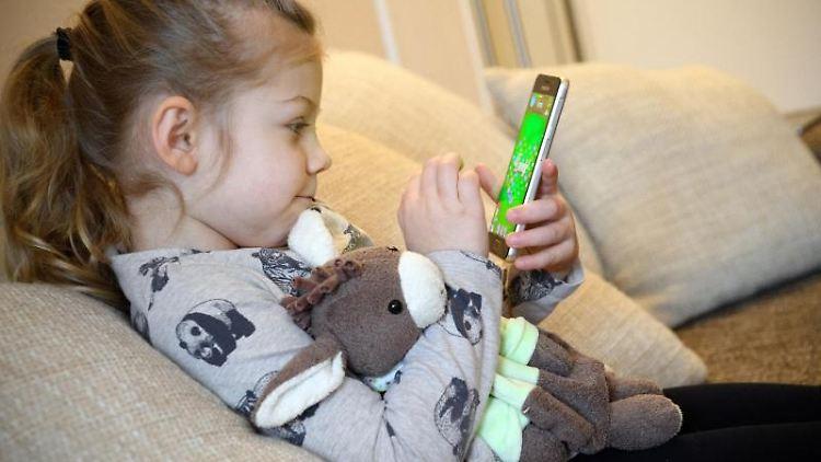 Ein Mädchen spielt ein Spiel auf einem Smartphone. Foto: Hans-Jürgen Wiedl/dpa-Zentralbild/dpa/Symbolbild