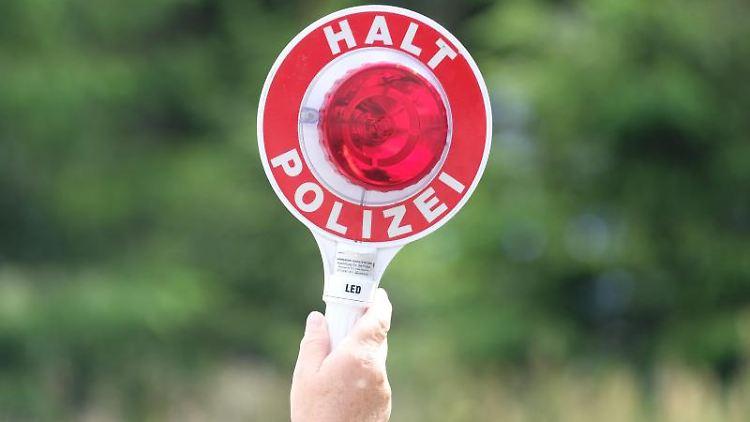 Eine Polizistin hält bei einer Verkehrskontrolle eine Winkerkelle in die Höhe. Foto: Sebastian Willnow/zb/dpa/Symbolbild
