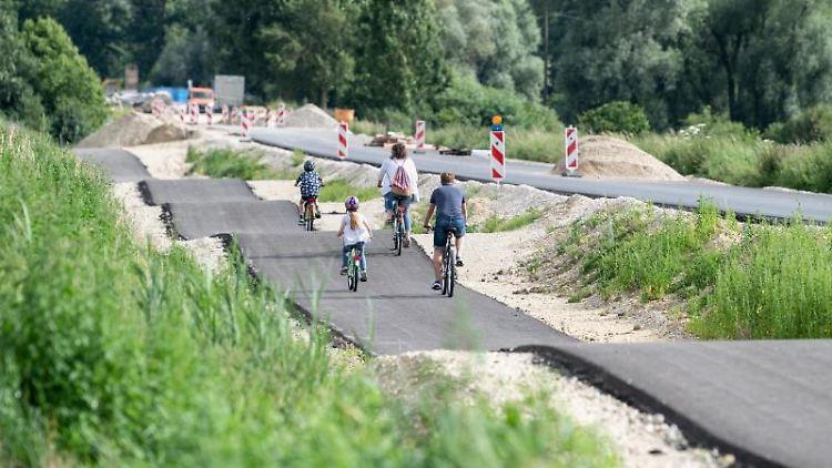 Eine Familie fährt einen als Buckelpiste angelegten Radweg entlang. Foto: Matthias Balk/dpa