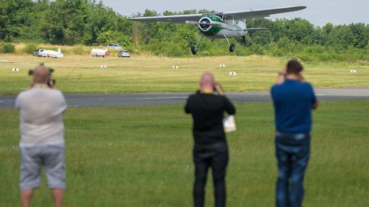 Eine Cessna landet vor Zuschauern auf dem Flugplatz. Foto: Candy Welz / Arifoto Ug/dpa-Zentralbild/ZB