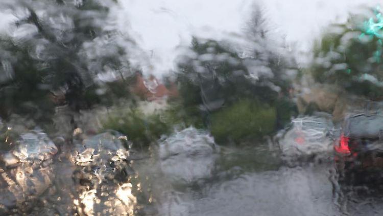 Autos fahren bei Regen über eine Straße. Foto: Wolfgang Kumm/dpa/Symbolbild