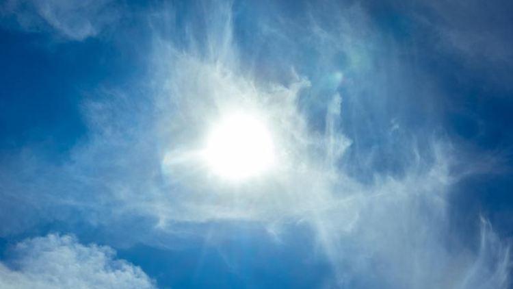 Die Sonne scheint am blauen Himmel durch Wolken hindurch. Foto: Markus Scholz/dpa/Symbolbild