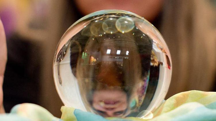 Eine Wahrsagerin blickt in eine Kristallkugel. Foto: Sebastian Kahnert/dpa/Symbolbild
