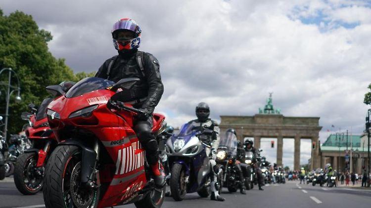 Motoradfahrer stehen auf derStraße des 17. Juni vor dem Brandenburger Tor. Foto: Jörg Carstensen/dpa