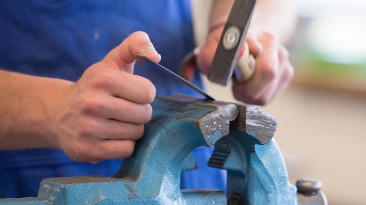Ein Auszubildender steht mit einem Hammer an einem Schraubstock. Foto: Sebastian Kahnert/dpa-Zentralbild/ZB/Symbolbild