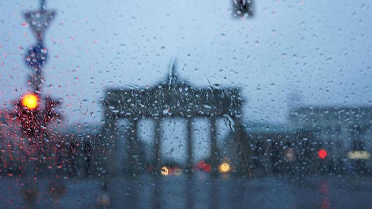 Durch eine mit Regentropfen bedeckte Scheibe eines Autos ist das Brandenburger Tor zu sehen. Foto: Jörg Carstensen/dpa/Symbolbild