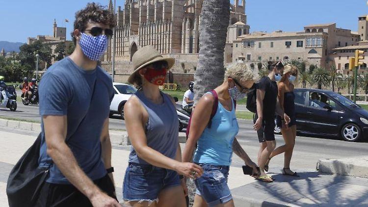 Junge Leute tragen einen Mund-Nasenschutz bei ihrem Gang durch Palma de Mallorca. Foto: Clara Margais/dpa/Archivbild
