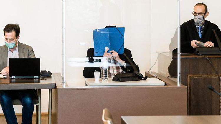 Angeklagter sitzt zwischen Arzt (l.) und Anwalt an mit Plexiglas geschütztem Platz im Gerichtssaal. Foto: Markus Scholz/dpa/Pool/dpa