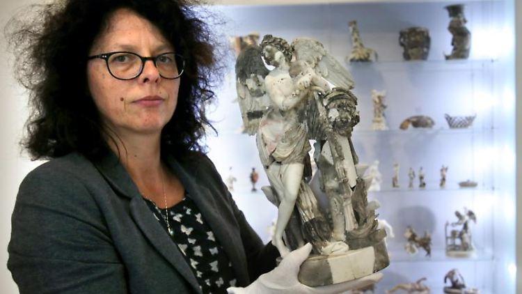 Elke Pretzel zeigt in der Kunstsammlung Neubrandenburg Überreste der Städtischen Kunstsammlung. Foto: Bernd Wüstneck/dpa-Zentralbild/dpa/Archivbild