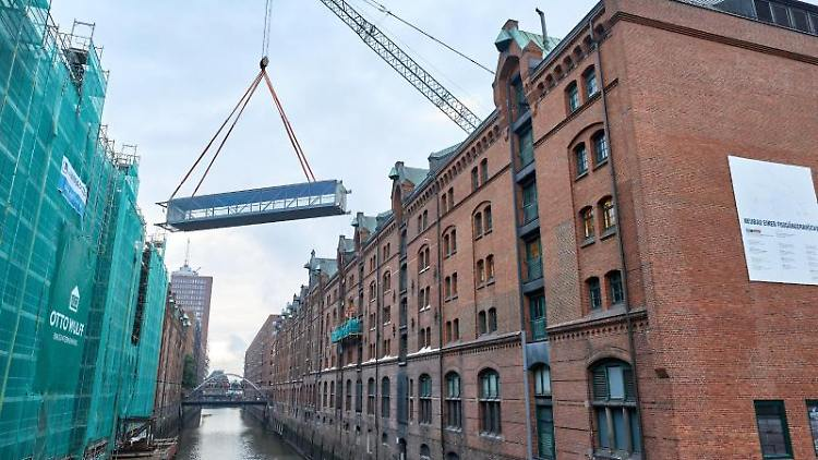 Eine Brücke schwebt an einem Kran über dem Kehrwiederfleet. Foto: Georg Wendt/dpa