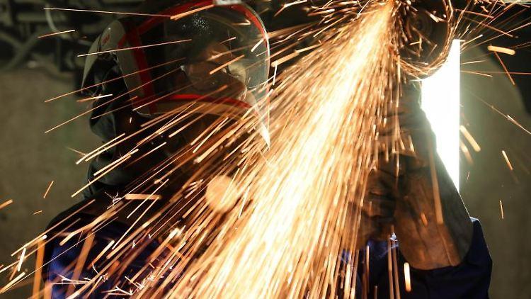 Ein Mitarbeiter eines Maschinenbauunternehmens schneidet Metallteile. Foto: Jan Woitas/dpa-Zentralbild/dpa/Illustration