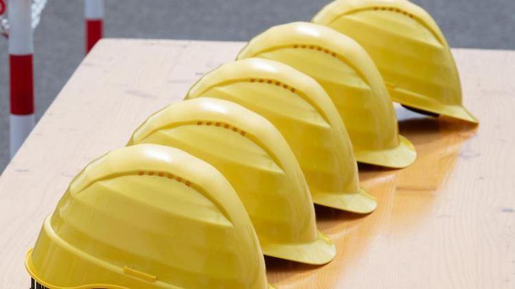 Gelbe Helme liegen nebeneinander auf einem Tisch. Foto: Soeren Stache/dpa/Symbolbild