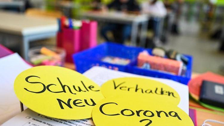 Schüler im Klassenzimmer und Papierschilder auf dem Lehrerpult. Foto: Felix Kästle/dpa/Archivbild