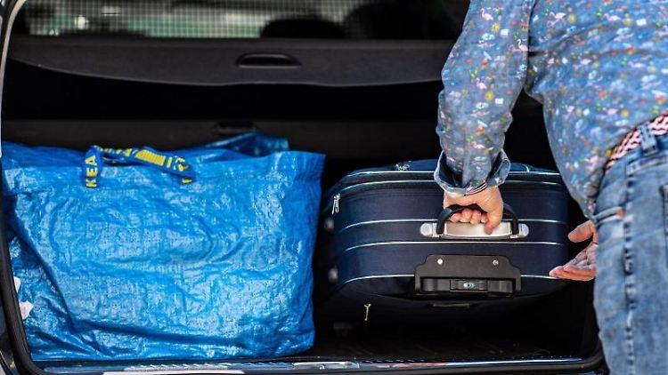 Gepackte Koffer werden in den Kofferraum seines Fahrzeuges geschoben. Foto: Guido Kirchner/dpa
