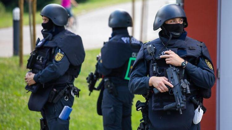 Beamte der Bereitschaftspolizei stehen vor einer Mehrzweckhalle. Foto: Philipp von Ditfurth/dpa/Archivbild