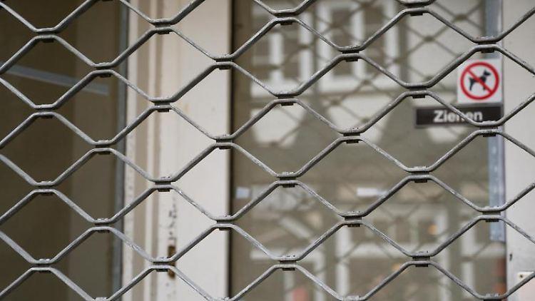 Ein leerer Geschäftsraum ist mit einem Eisengitter verriegelt. Foto: Christophe Gateau/dpa/Archivbild