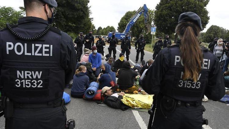 Demonstranten sitzen auf der L277, um den Abriss der Straße zu verhindern. Foto: Roberto Pfeil/dpa