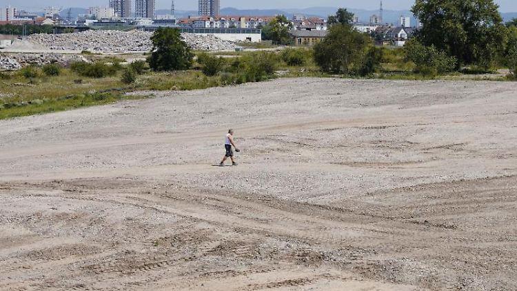 Ein Bauarbeiter geht über eine Baufläche für die Bundesgartenschau 2023. Foto: Uwe Anspach/dpa