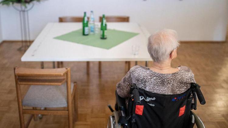 Eine ältere Frau sitzt in einem Pflegeheim in ihrem Rollstuhl vor einem Tisch. Foto: Marcel Kusch/dpa/Symbolbild