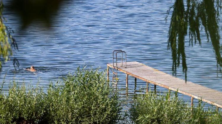 Ein Mann schwimmt neben einem Badesteg im Hasse-See. Foto: Jan Woitas/dpa-Zentralbild/dpa/Archivbild