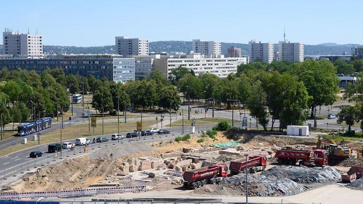 Baufahrzeuge stehen auf dem Ferdinandplatz an den archäologischen Ausgrabungen hinter einem Parkplatz. Foto: Sebastian Kahnert/dpa-Zentralbild/dpa