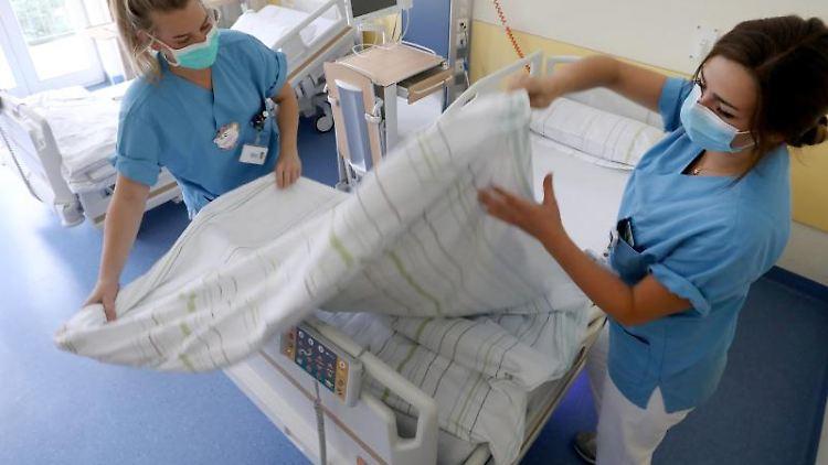 Zwei Schwestern richten in der Kardioligschen Wachstation der Universitätsmedizin ein Bett her. Foto: Bernd Wüstneck/dpa-Zentralbild/dpa