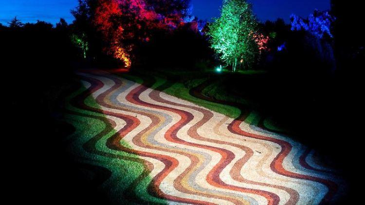 Wellenförmige Strukturen werden im Park der Gärten auf einen Weg projiziert. Foto: Hauke-Christian Dittrich/dpa