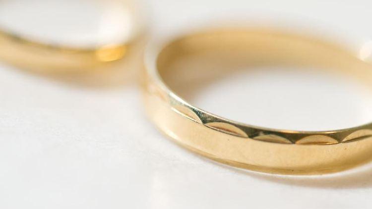 Zwei Eheringe liegen auf einem Tisch. Foto: picture alliance / dpa/Symbolbild