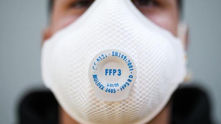 Ein junger Mann trägt eine Atemschutzmaske. Foto: Christoph Schmidt/dpa/Symbolbild