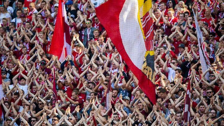 Fans vom FC Bayern München klatschen in die Hände. Foto: Lino Mirgeler/dpa