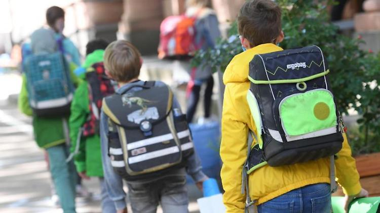 Schülerinnen und Schüler einer vierten Klasse gehen auf dem Schulhof ins Schulgebäude. Foto: Arne Dedert/dpa/Symbolbild