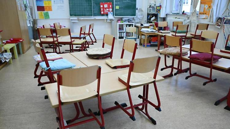 Stühle sind in einem leeren Klassenzimmer auf den Tische abgestellt. Foto: Arne Dedert/dpa/Archiv