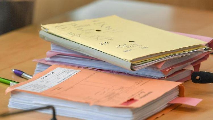 Akten liegen in einem Verhandlungssaal auf einem Tisch. Foto: Patrick Pleul/dpa-Zentralbild/ZB/Archivbild