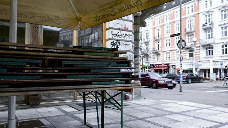 Biertische sind vor den Cafes an der Roten Flora im Schanzenviertel gestapelt. Foto: Axel Heimken/dpa