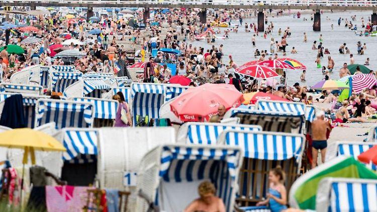 Badegäste geniessen im Juli den Nachmittag am Ostseestrand. Foto: Markus Scholz/dpa