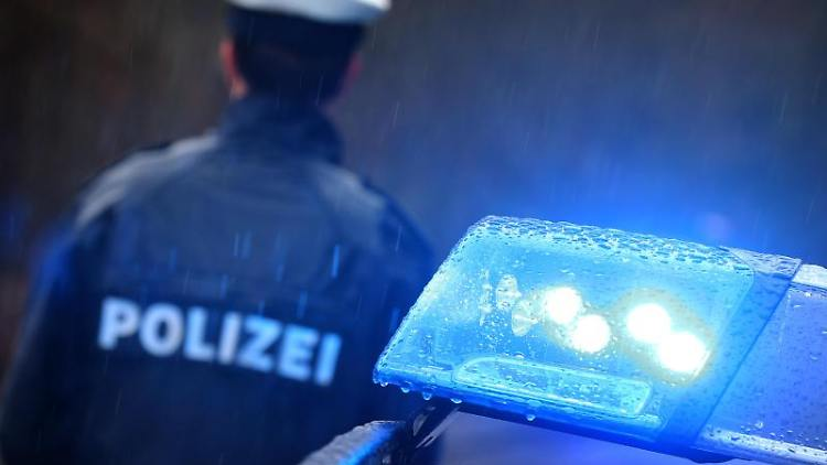 Ein Polizist steht vor einem Streifenwagen dessen Blaulicht aktiviert ist. Foto: Karl-Josef Hildenbrand/dpa/Archiv