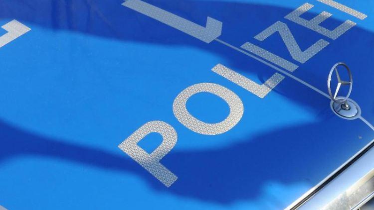 Der Schatten eines Polizisten fällt auf ein Polizeiauto. Foto: Franziska Kraufmann/dpa/Symbolbild
