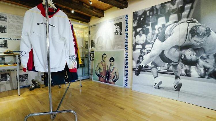 Kleidungsstücke hängen in den Räumen des Deutschen Ringermuseums. Foto: Uwe Anspach/dpa/Archivbild