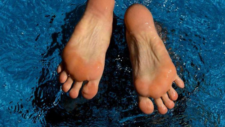 Ein Mann taucht in einem Freibad bei hochsommerlichen Temperaturen in das kühle Wasser. Foto: Ralf Hirschberger/dpa-Zentralbild/dpa/Symbolbild