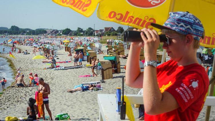 Eine Mitarbeiterin der DLRGbeobachtet einen vollen Strandabschnitt in der Dorfschaft Haffkrug. Foto: Gregor Fischer/dpa