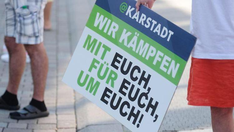 Die Teilnehmerin einer Protestaktion hält vor dem Karstadt-Warenhaus in Dessau-Roßlau ein Schild. Foto: Sebastian Willnow/dpa-Zentralbild/dpa