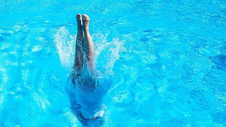 Eine Frau taucht in einem Stuttgarter Schwimmbad ins Becken ein. Foto: Sebastian Gollnow/dpa/Archivbild