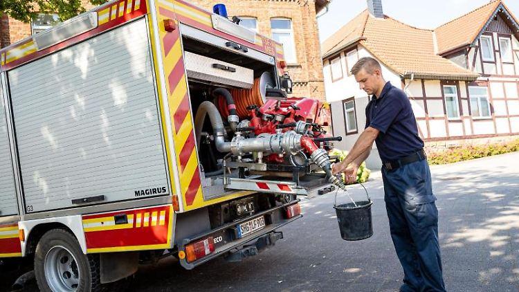 Einsatzkräfte der Freiwilligen Feuerwehr Lauenau zapfen Löschwasser aus einem Einsatzfahrzeug-Tank. Foto: Moritz Frankenberg/dpa