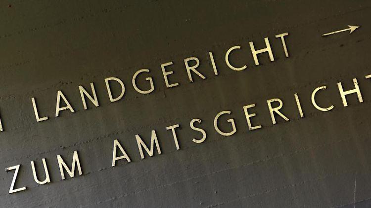 An der Wand eines Gerichtsgebäudes prangt ein Wegweiser zum Land- und Amtsgericht. Foto: Uwe Zucchi/dpa/archiv