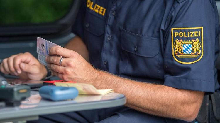 Ein Beamter der bayerischen Grenzpolizei kontrolliert am Grenzübergang Kirchdorf Dokumente von Autofahrern. Foto: Lino Mirgeler/dpa/Archiv