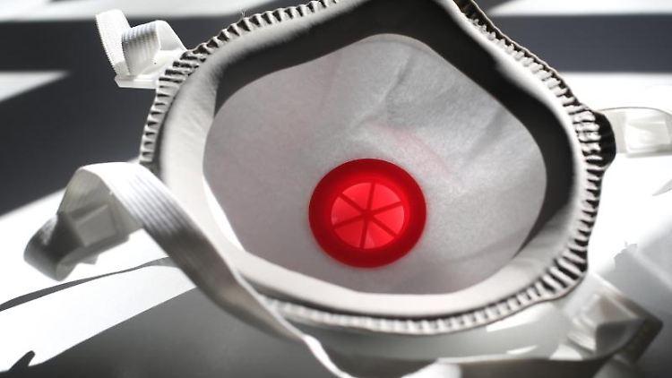 Eine FFP3 Atemschutzmaske liegt auf einem Tisch im Sonnenschein. Foto: Karl-Josef Hildenbrand/dpa