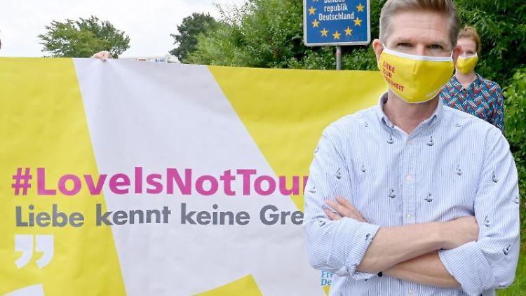 Mit einer Schutzmaske steht Heiner Garg (FDP) bei einer Demonstration am Grenzübergang Padborg. Foto: Carsten Rehder/dpa/Archivbild
